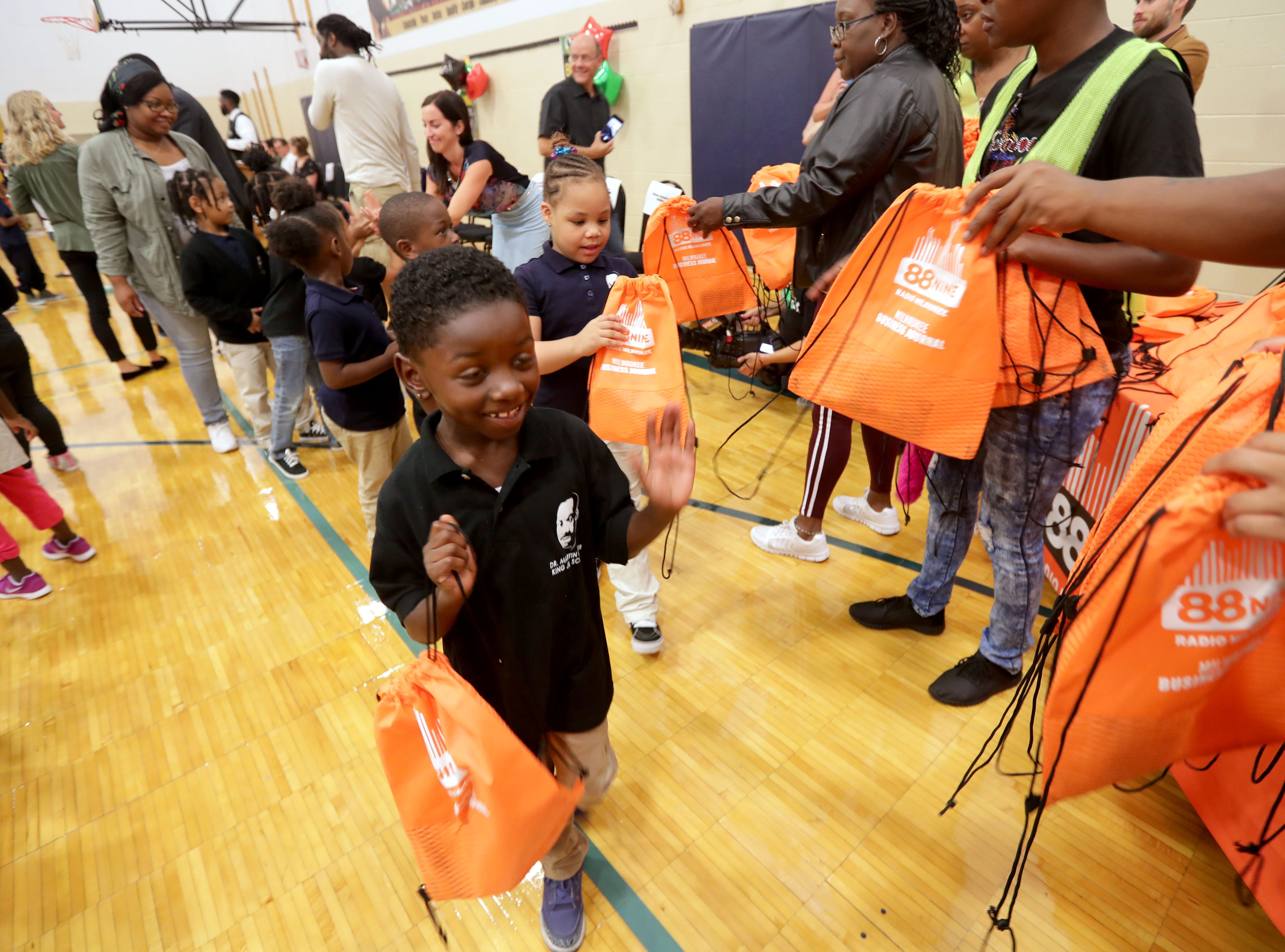 Raquon Totton, a Dr. Martin Luther King Jr. student, gets his backpack as volunteers pass them out.