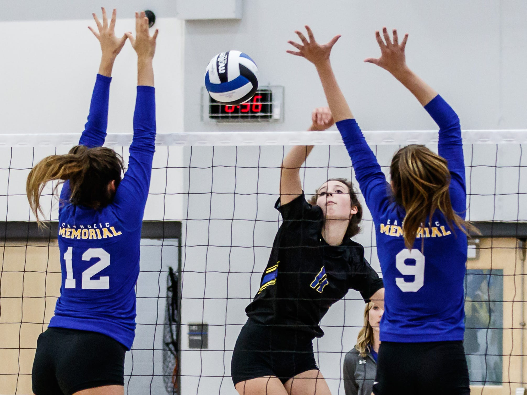 Mukwonago sophomore Marissa Reynolds (11) hits the gap between Catholic Memorial's Jenna Weinfurt (12) and Kaitlyn Riley (9) during the match at Mukwonago on Tuesday, Sept. 11, 2018.