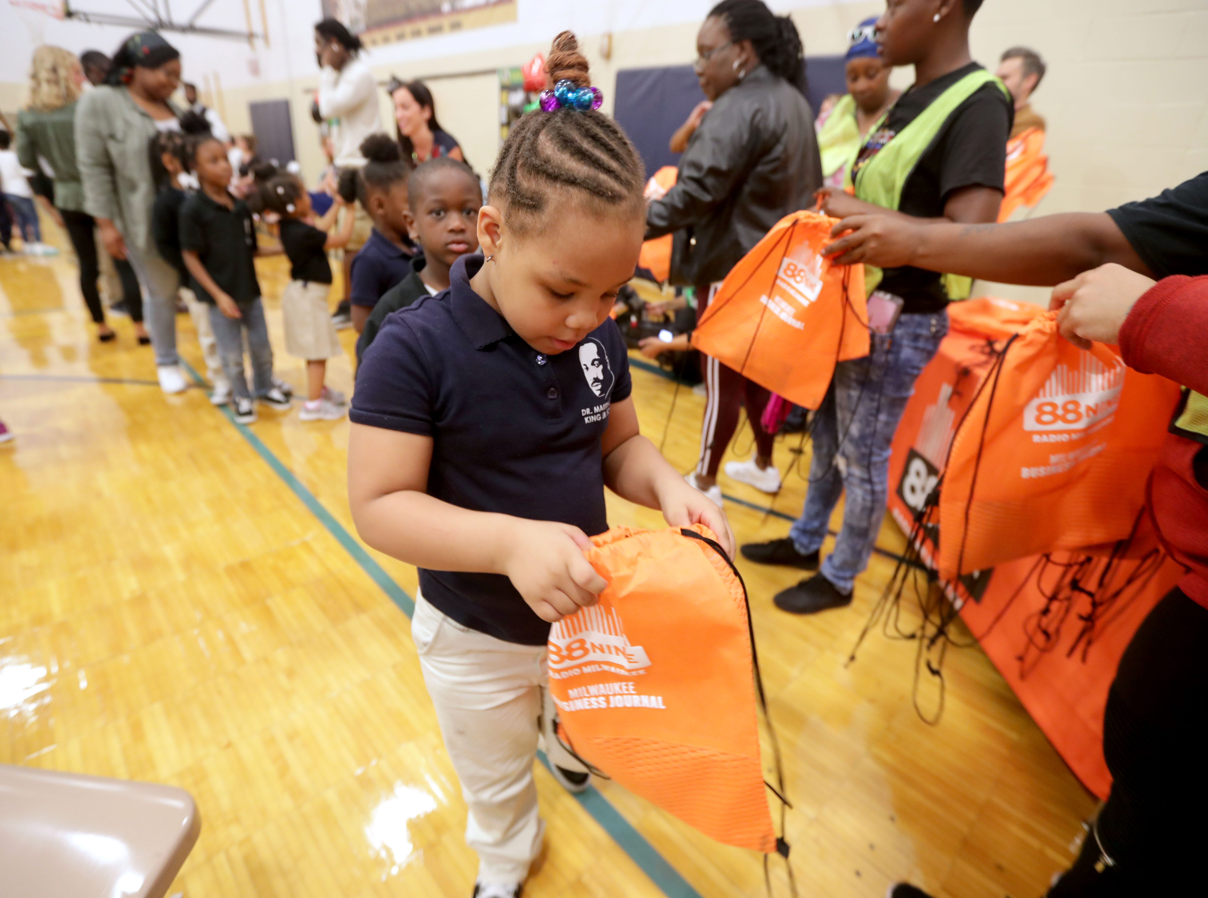 Anihya Mooney-Good, a Dr. Martin Luther King Jr. student, looks in her backpack after receiving it Wednesday at the school.