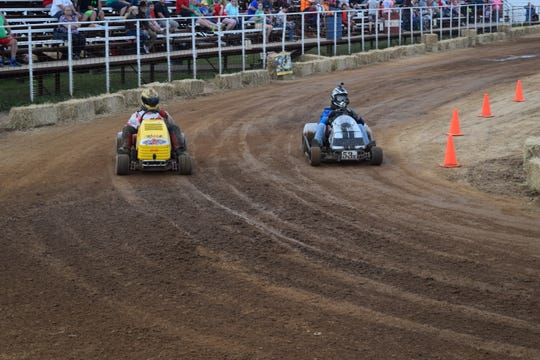 Two drivers round a corner during the 2017 Baxter County Fair lawnmower races. Heavily modified racing lawnmowers usually sit lower to the ground and have go-kart tires.
