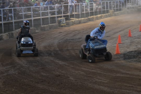Drivers lean into a corner during a lawnmower race at the Saddle Club Arena.