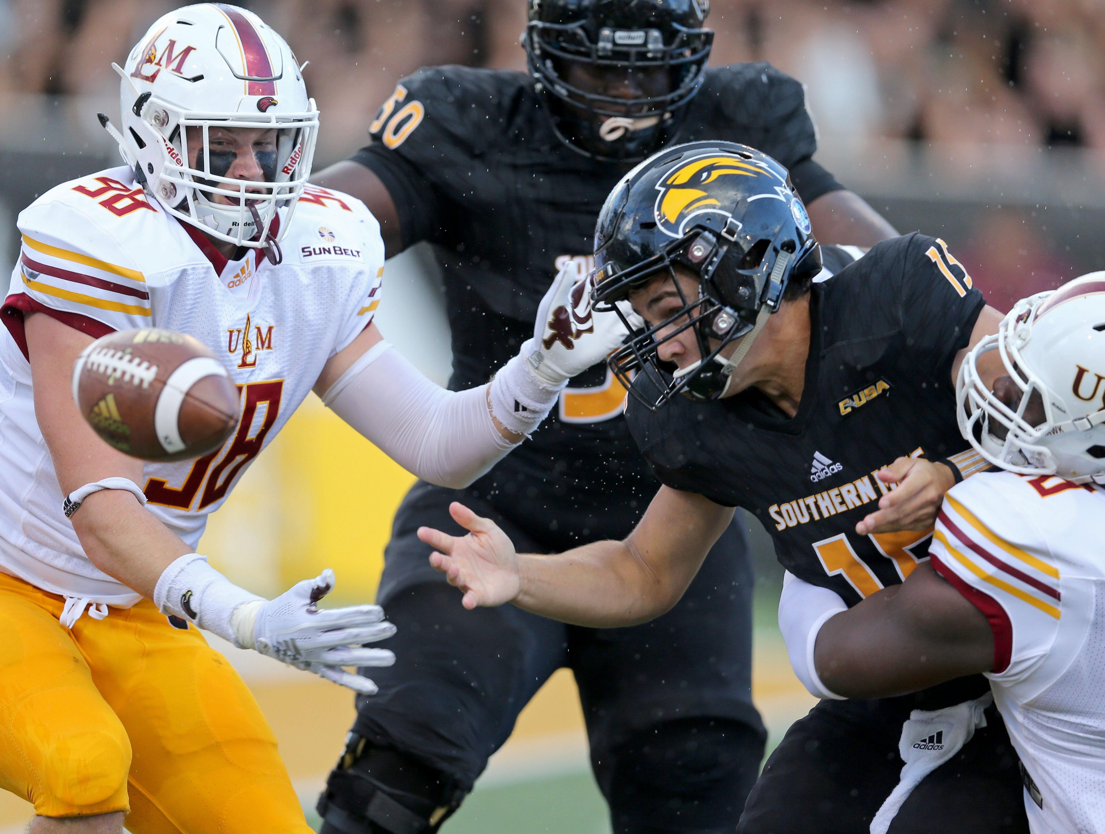 Sep 8, 2018; Hattiesburg, MS, USA; Southern Miss Golden Eagles quarterback Jack Abraham (15) fumbles after being hit by Louisiana Monroe Warhawks defensive lineman Donald Louis Jr. (58), right, at M. M. Roberts Stadium. Louisiana Monroe Warhawks defensive end Sam Miller (98), left, recovered the ball in the end zone for a touchdown. Mandatory Credit: Chuck Cook-USA TODAY Sports