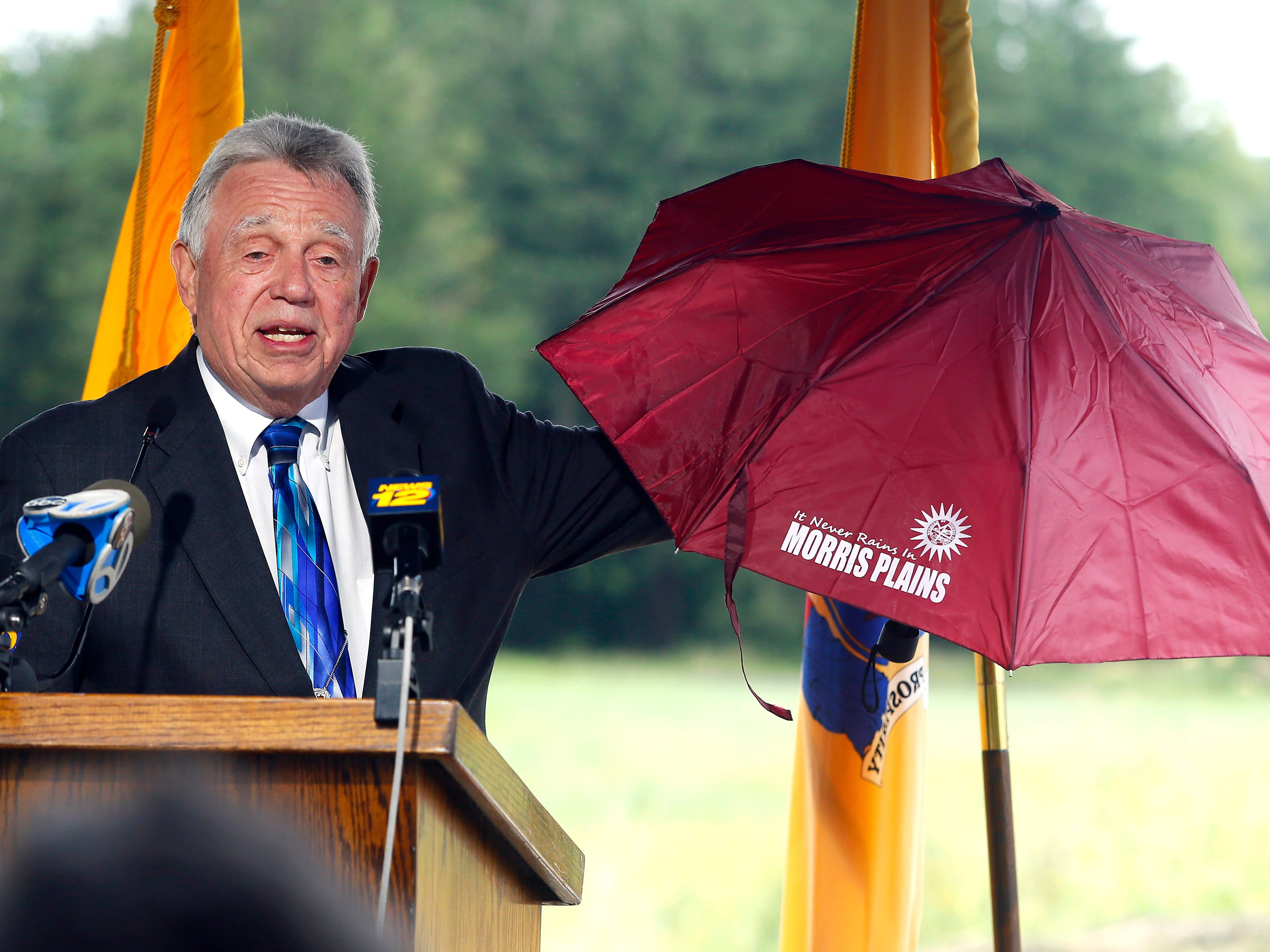 Morris Plains Mayor Frank Druetzler gifts an umbrella with his unofficial motto to former New Jersey Governor Chris Christie as Morris County freeholders formally open Gov. Chris Christie Drive, a new main access road to Central Park of Morris County. September 12, 2018, Morris Plains, NJ