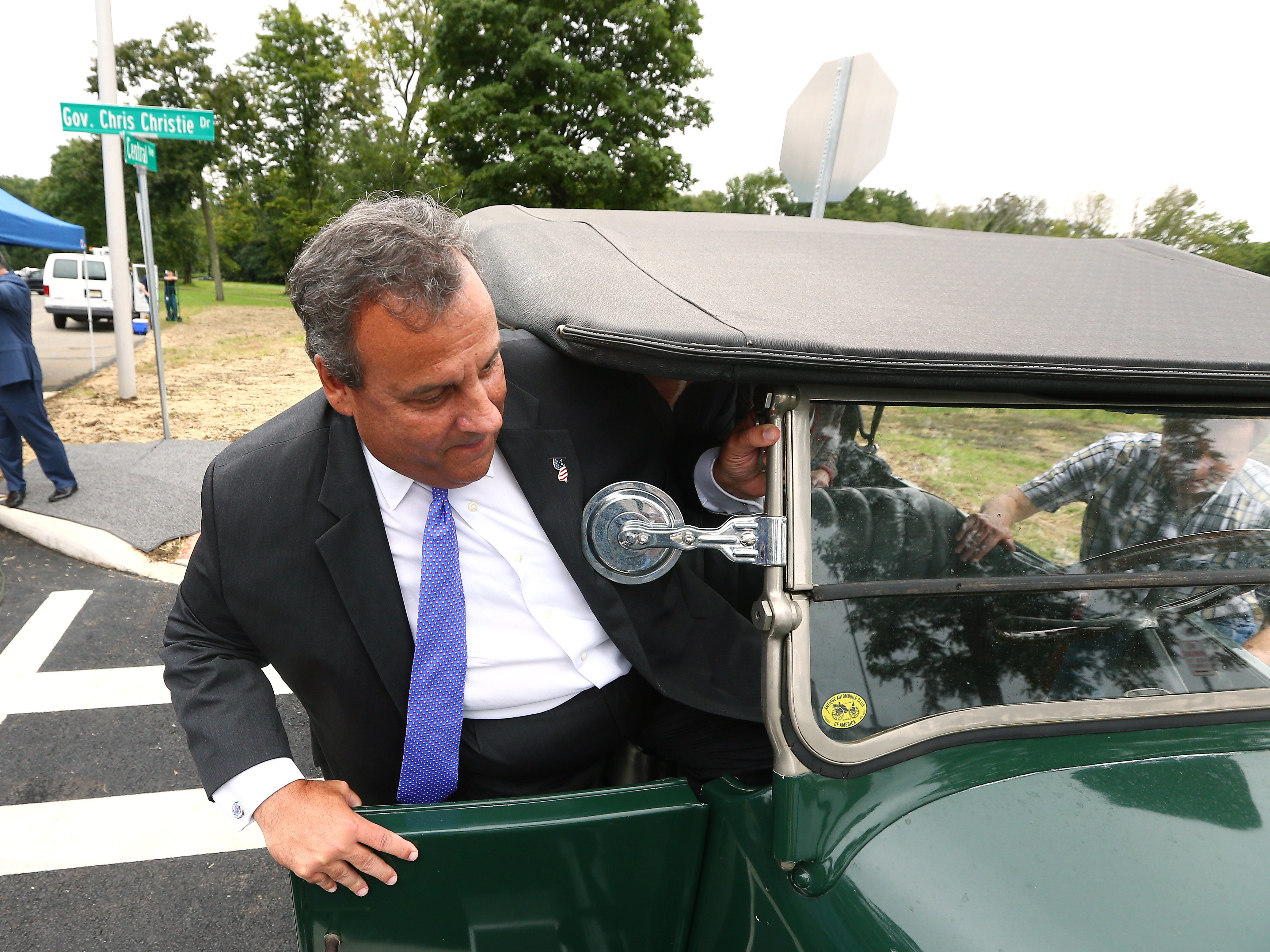 Former New Jersey Governor Chris Christie climbs into a 1922 Franklin Model 10A to take an inaugural ride on his newly dedicated Gov. Chris Christie Drive, a new main access road to Central Park of Morris County. September 12, 2018, Morris Plains, NJ