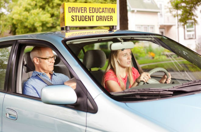 A young teenager girl behind the wheel of a car, learning to drive while a driver's training examiner scores performance in a student driving examination in the Midwest, USA.