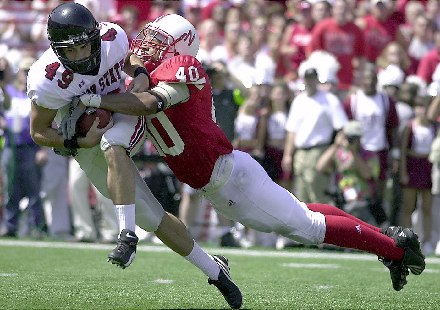 Troy State punter Lance Lieb (49) is tackled by Nebraska's Lannie Hopkins after a bad snapped forced Lieb to try and run in the first half of the 2001 game between the Trojans and Cornhuskers.
