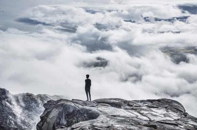 Young man standing over the clouds at Los Andes, Bariloche, Patagonia