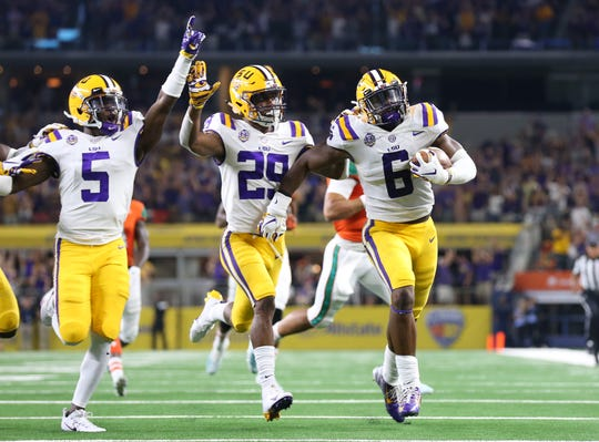 LSU linebacker Jacob Phillips (6) returns an interception for a touchdown as teammates cornerback Greedy Williams (29) and Kary Vincent Jr (5) celebrate against Miami at AT&T Stadium on Sept. 2, 2018, in Arlington, Texas.