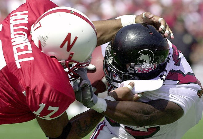 Troy State running back LeBarron Black and Nebraska's T.J. Hollowell tangle as black fights for yards when the teams played in 2001.