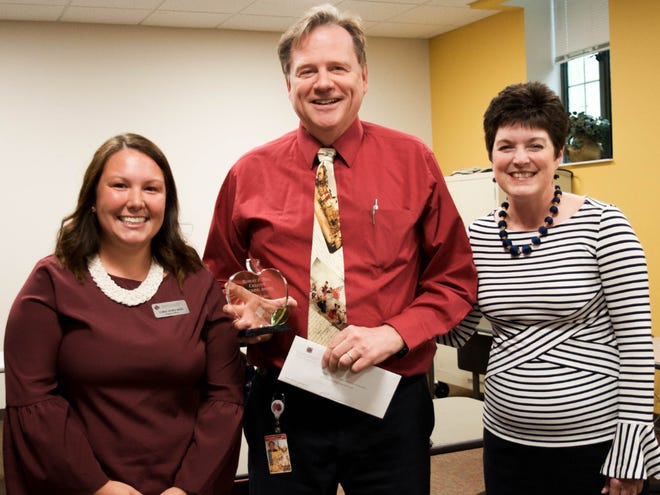 John Marsh, a history teacher at the Indiana Academy for Science, Mathematics and Humanities, has been named the recipient of the inaugural Robert P. Bell Creative Teaching Award from the Community Foundation of Muncie and Delaware County. Marsh (center) poses with foundation program officer, Carly Acree-King (left), and president, Kelly K. Shrock (right).