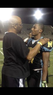 Willie Brooks Jr. congratulates his son Khalil Brooks following one of Khalil's games at Benjamin E. Mays High School.