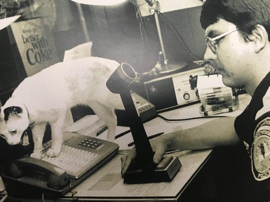 Former Brentwood Police Department dispatcher Jeff Mitchell works while the department cat, Major, explores his desk in an undated photo.