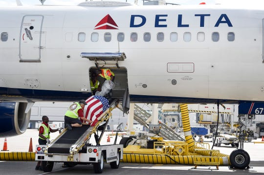 TSA staff remove the remains of Harold DeMoss, a pilot who died during WWII off the plane,  from the cargo department of Delta flight #1066, at the Nashville International Airport in Nashville, Tenn., Wednesday, Sept. 12, 2018.