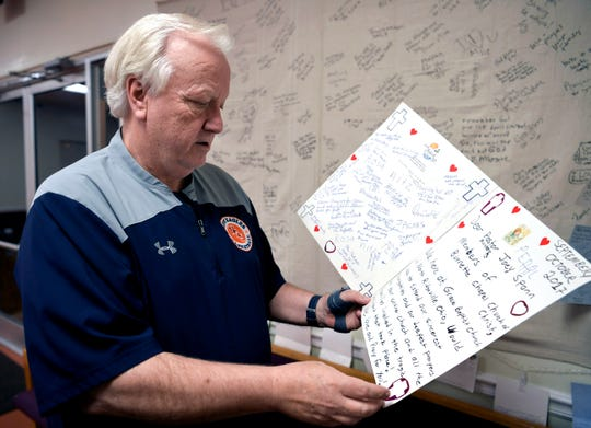 Minister Joey Spann reads a card sent to Burnette Chapel Church of Christ after a gunman opened fire on his congregation a year ago.