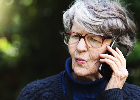 Senior Woman Using Mobile Phone Frowns