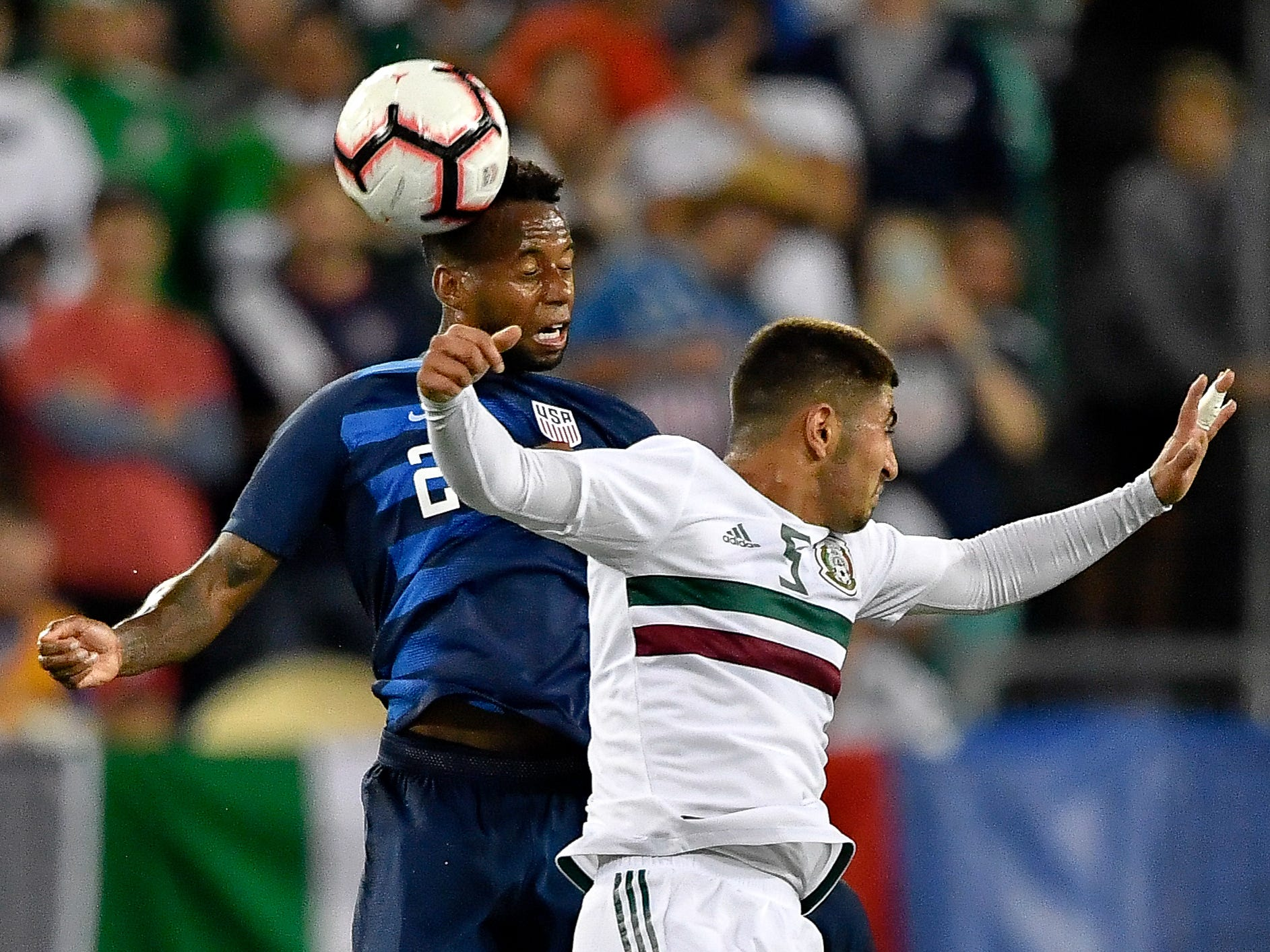 Mexico midfielder Victor Guzman (5) and USA midfielder Kellyn Acosta (23) leap for a header during the first half at Nissan Stadium in Nashville, Tenn., Tuesday, Sept. 11, 2018.