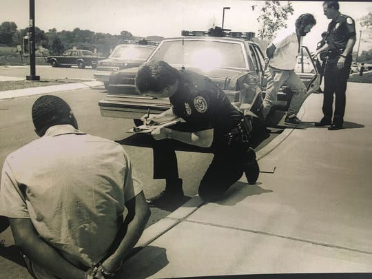 Jeff Hughes, now chief of the Brentwood Police Department, and former officer Joey Kimble, in the background, arrest employees with the city's public works department in 1988 after an undercover investigation found several workers were selling cocaine and marijuana out of the city garage.