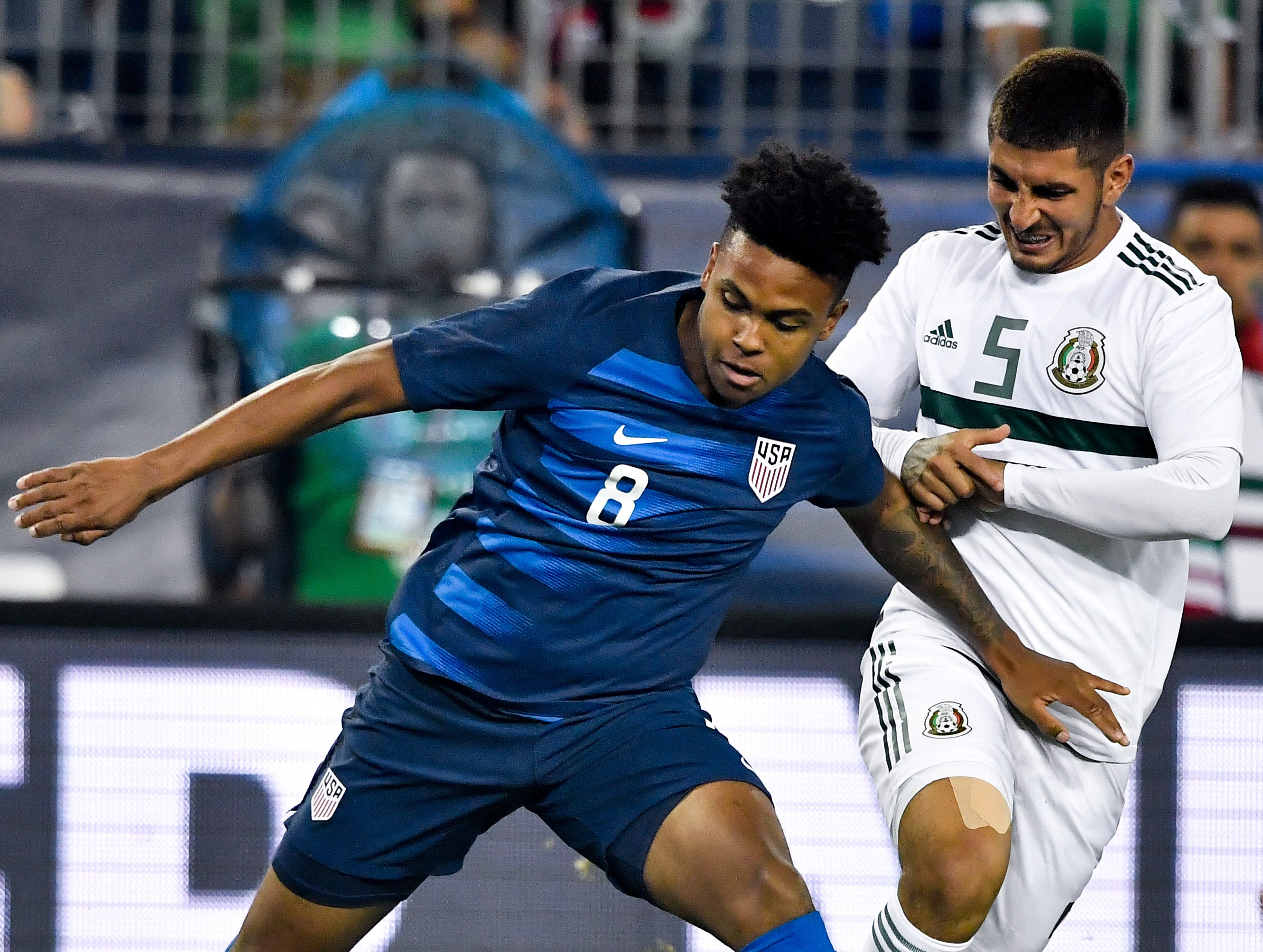 USA midfielder Weston McKennie (8) fights for the ball with Mexico midfielder Victor Guzman (5) during the first half at Nissan Stadium in Nashville, Tenn., Tuesday, Sept. 11, 2018.