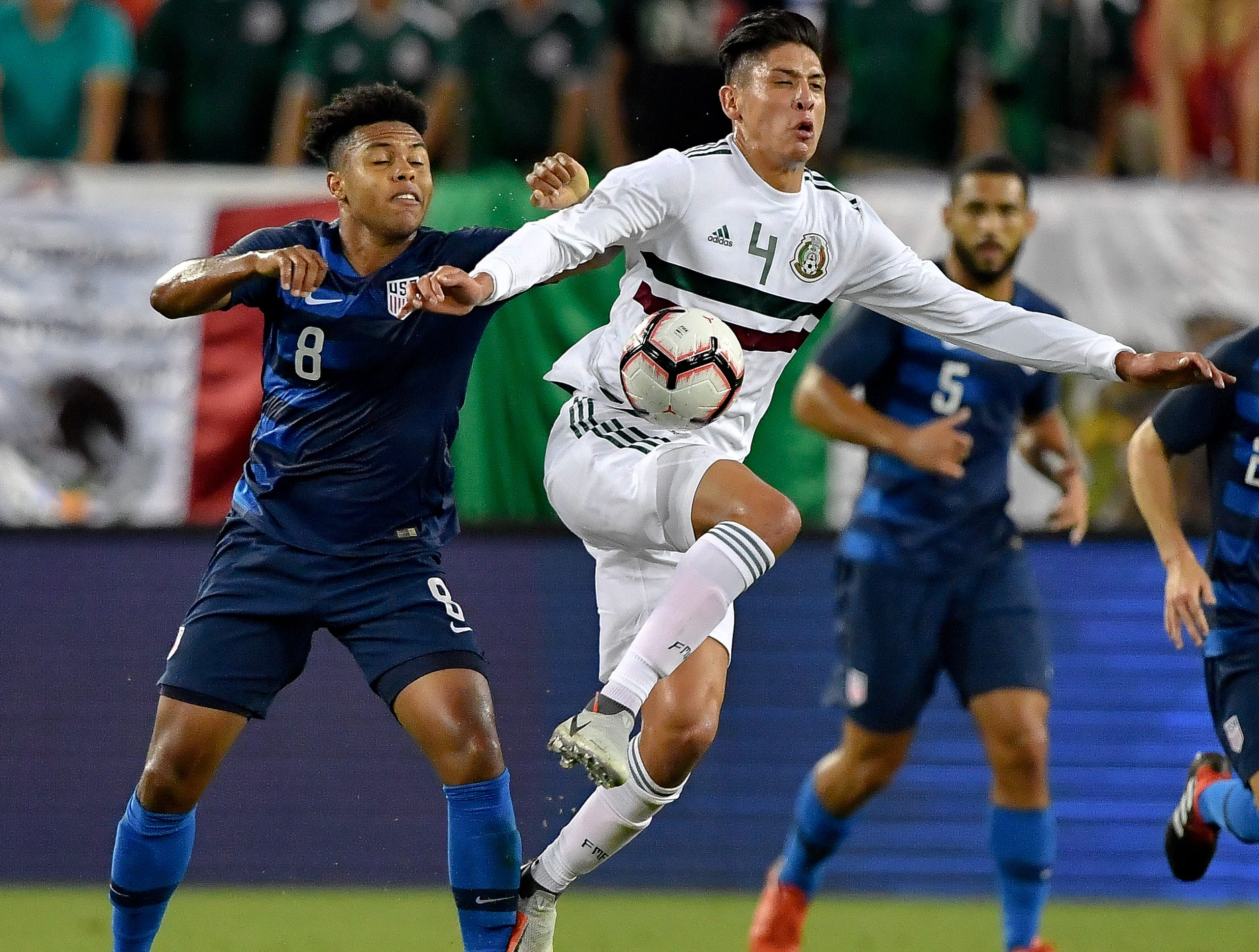 Mexico defender Edson Alvarez (4) jumps for the ball in front of USA midfielder Weston McKennie (8) during the first half at Nissan Stadium in Nashville, Tenn., Tuesday, Sept. 11, 2018.