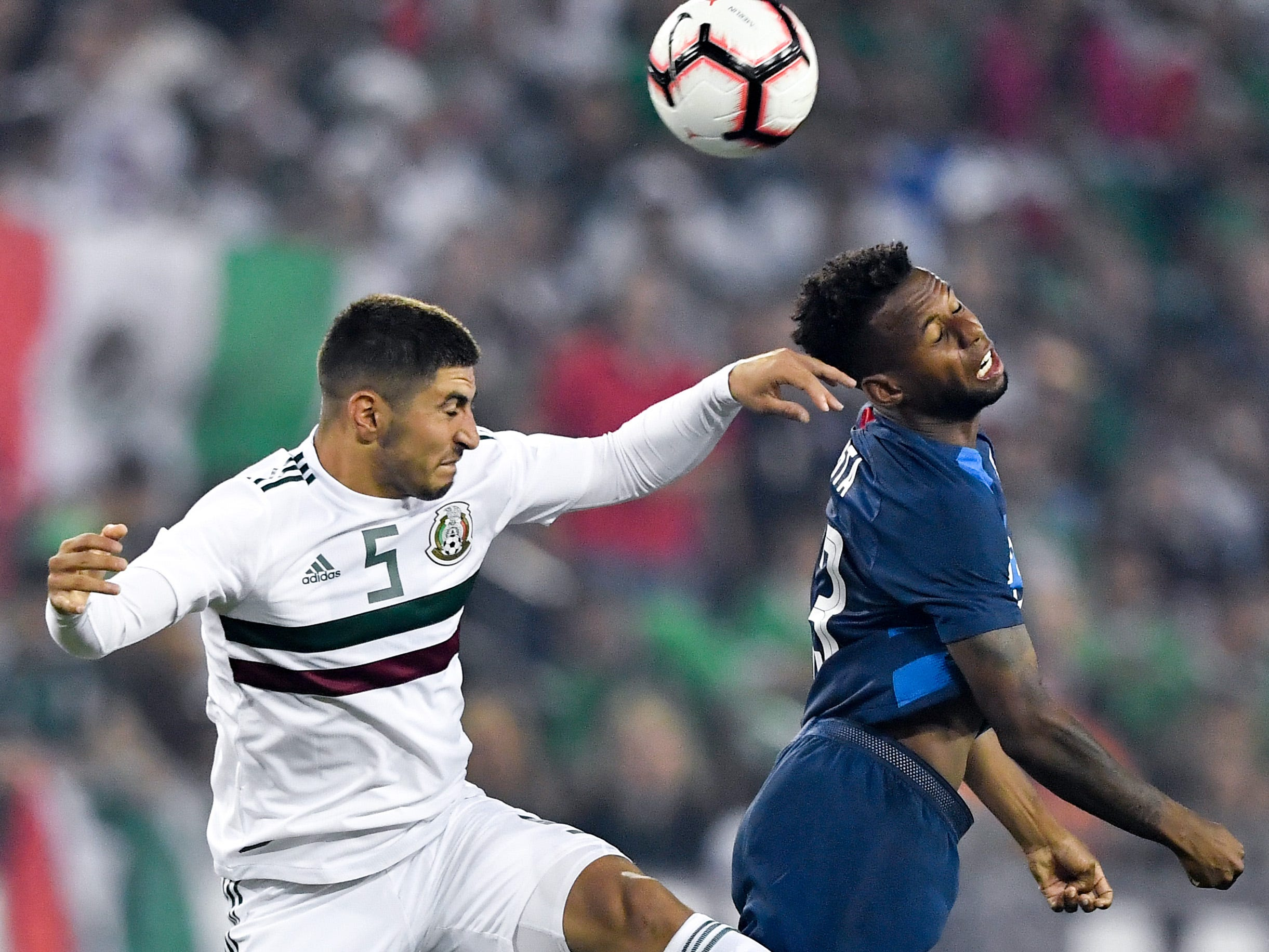 Mexico midfielder Victor Guzman (5) and USA midfielder Kellyn Acosta (23) go for a header during the first half at Nissan Stadium in Nashville, Tenn., Tuesday, Sept. 11, 2018.