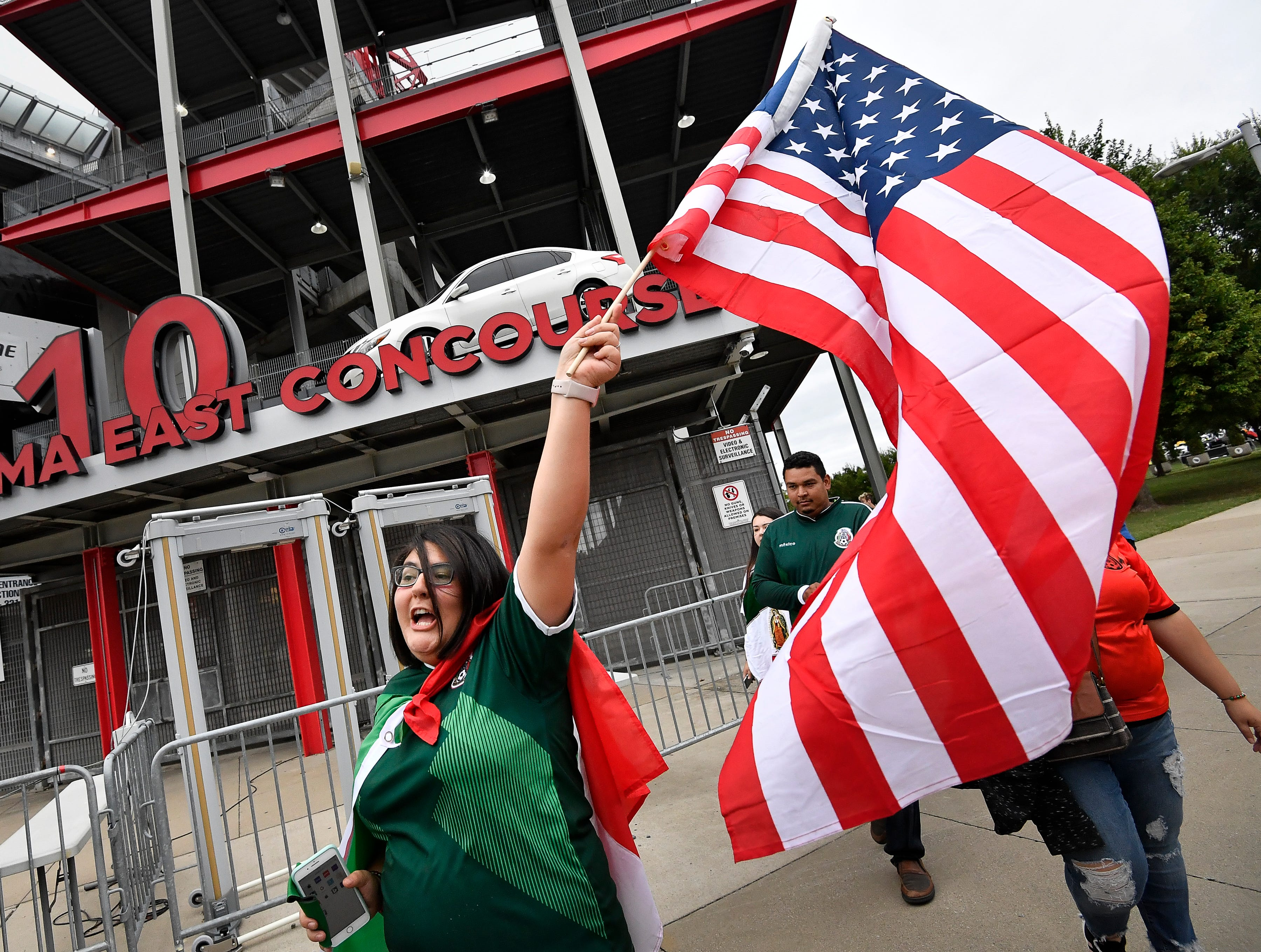 Mexican soccer fan Connie Mathies waves the American flag before the USA vs. Mexico soccer match at Nissan Stadium Tuesday, Sept. 11, 2018, in Nashville, Tenn.