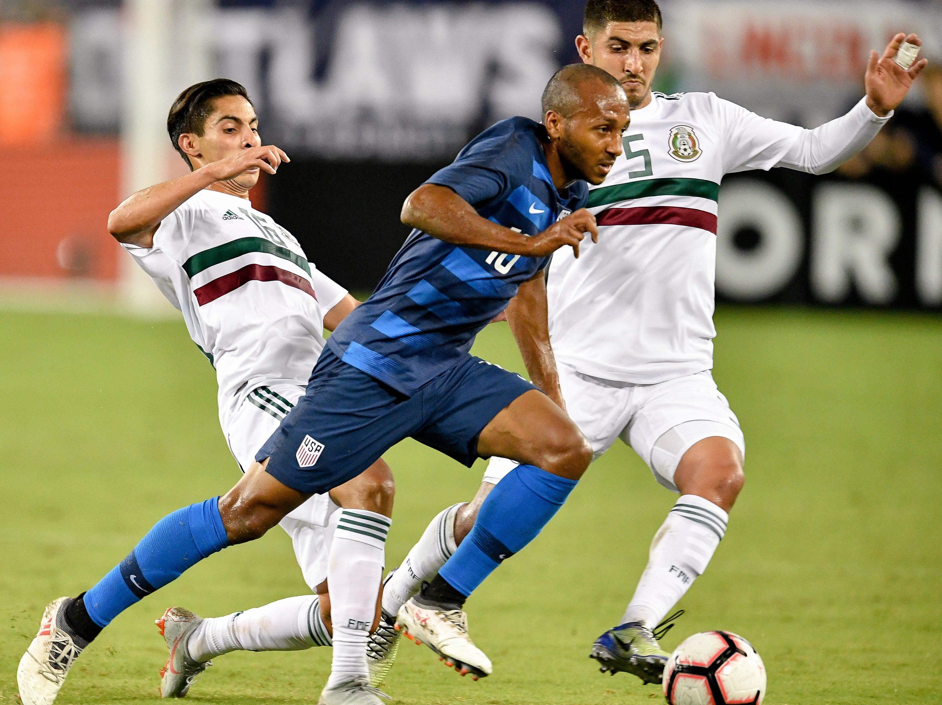 USA midfielder Julian Green (16) advances through Mexico midfielder Erick Aguirre (16) and midfielder Victor Guzman (5) during the second half at Nissan Stadium in Nashville, Tenn., Tuesday, Sept. 11, 2018.