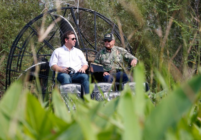 Republican candidate for Florida Governor Ron DeSantis, left, chats with Gladesman and former Florida Fish and Wildlife Conservation commissioner Ron Bergeron during an airboat tour of the Florida Everglades, Wednesday, Sept. 12, 2018, in Fort Lauderdale, Fla. (AP Photo/Wilfredo Lee)