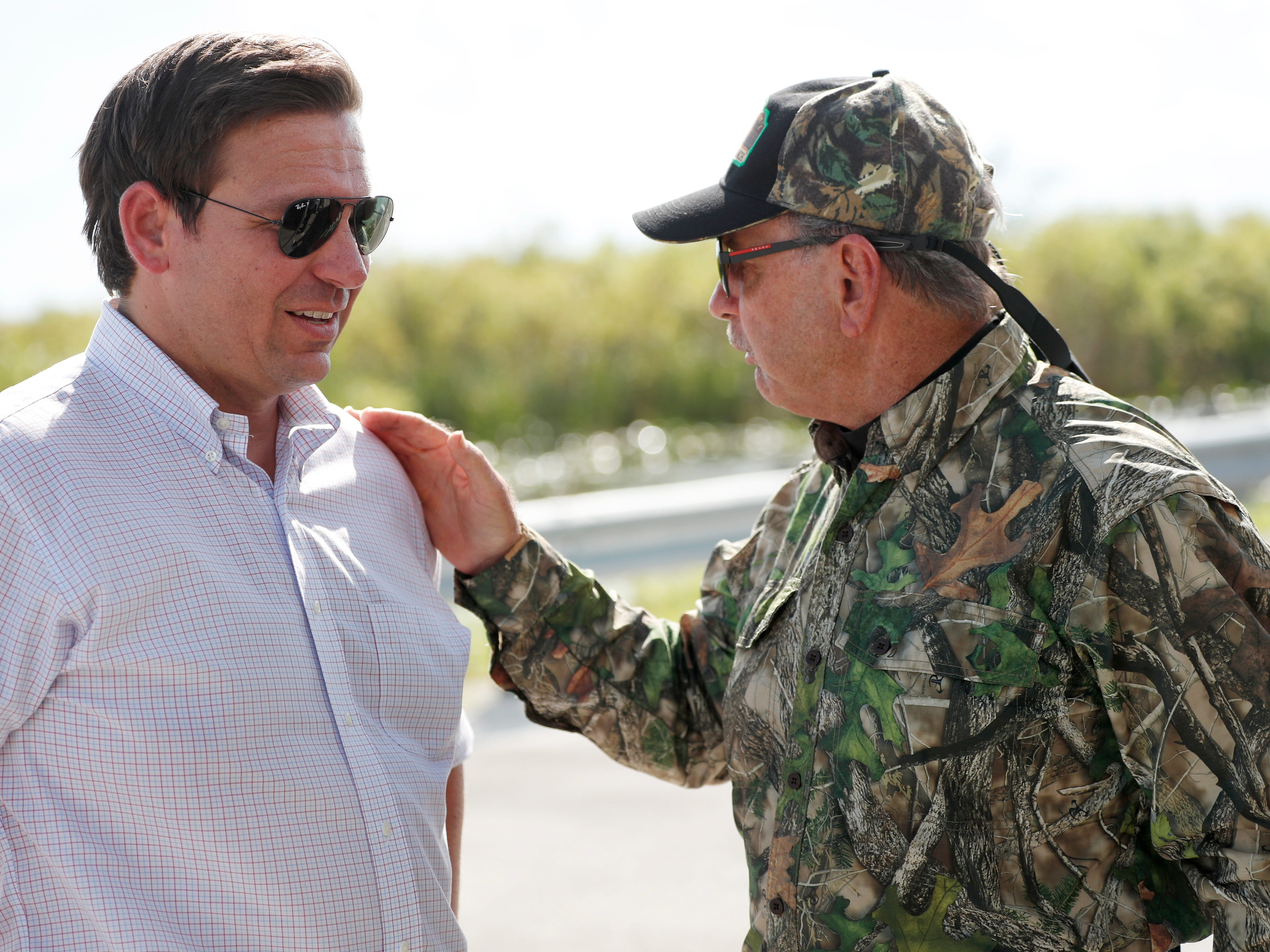 Republican candidate for Florida Governor Ron DeSantis, chats with Gladesman and former Florida Fish and Wildlife Conservation commissioner Ron Bergeron after an airboat tour of the Florida Everglades, Wednesday, Sept. 12, 2018, in Fort Lauderdale, Fla. (AP Photo/Wilfredo Lee)