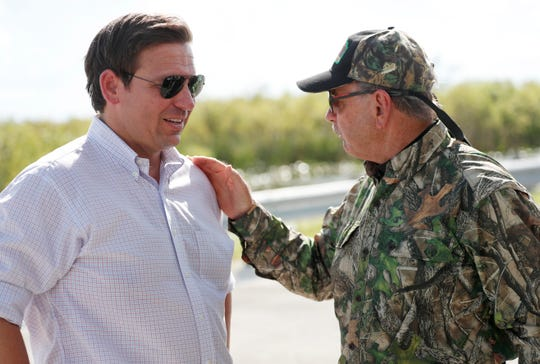 Then-Republican candidate for Florida governor Ron DeSantis chats with former Florida Fish and Wildlife Conservation commissioner Ron Bergeron after an airboat tour of the Florida Everglades, Wednesday, Sept. 12, 2018, in Fort Lauderdale. (AP Photo/Wilfredo Lee)