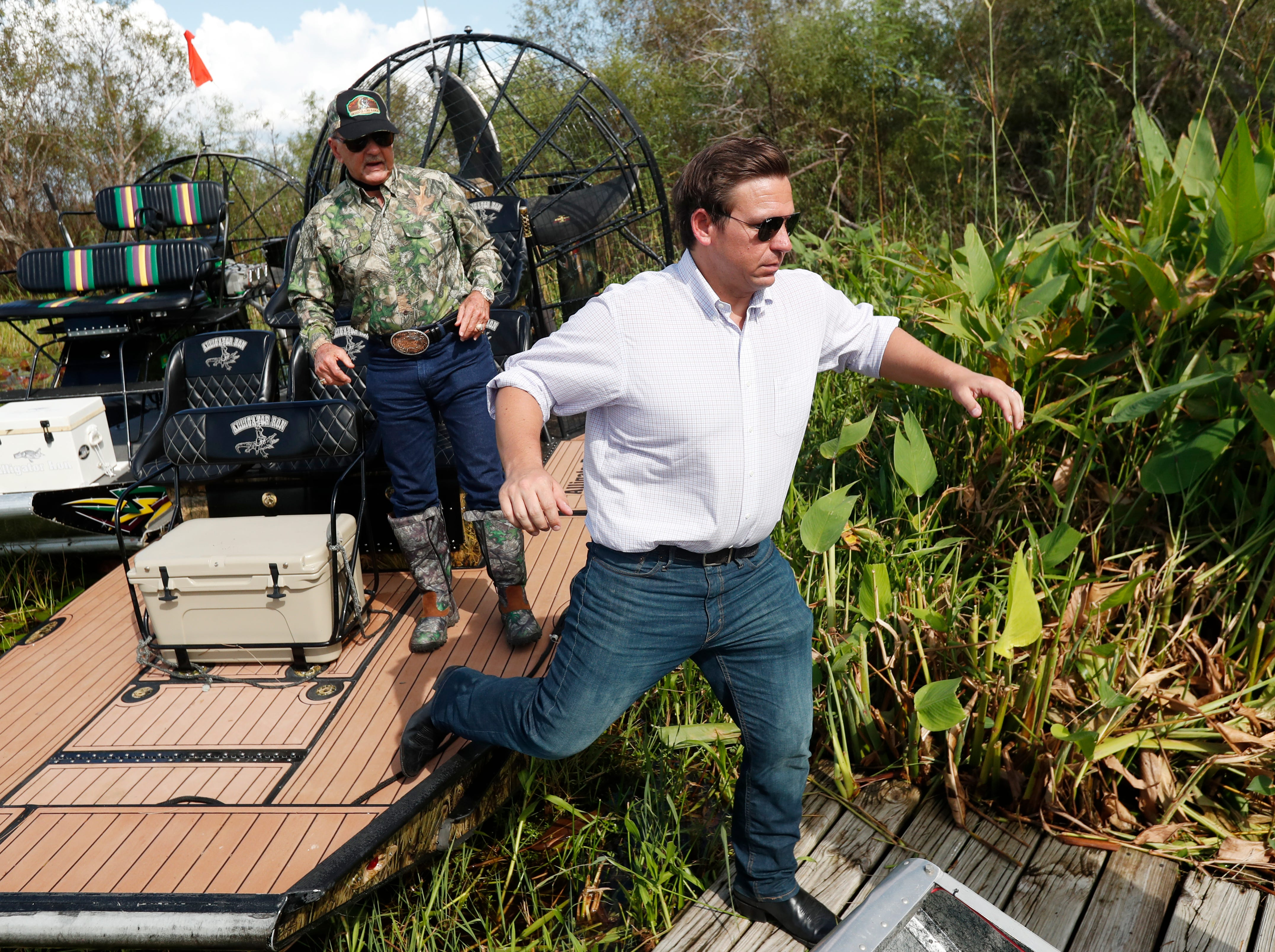 Republican candidate for Florida Governor Ron DeSantis, gets off an airboat with Gladesman and former Florida Fish and Wildlife Conservation commissioner Ron Bergeron after a tour of the Florida Everglades, Wednesday, Sept. 12, 2018, in Fort Lauderdale, Fla. (AP Photo/Wilfredo Lee)