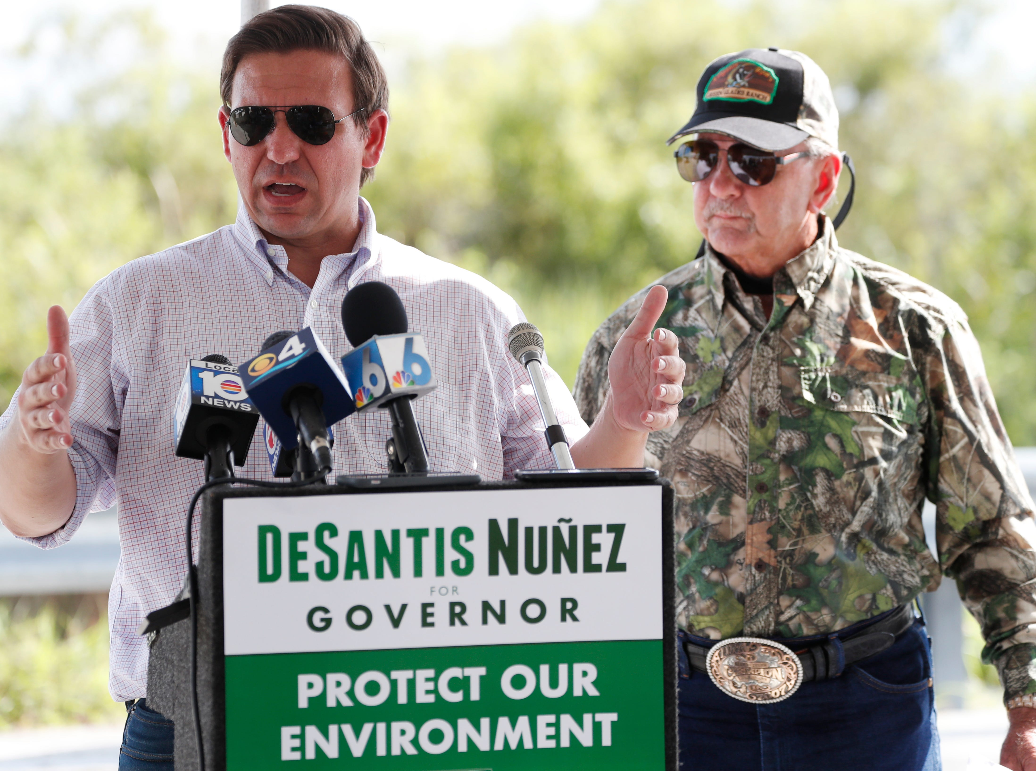 Republican candidate for Florida Governor Ron DeSantis, left, speaks during a news conference along with Gladesman and former Florida Fish and Wildlife Conservation commissioner Ron Bergeron, right, after an airboat tour of the Florida Everglades, Wednesday, Sept. 12, 2018, in Fort Lauderdale, Fla. (AP Photo/Wilfredo Lee)
