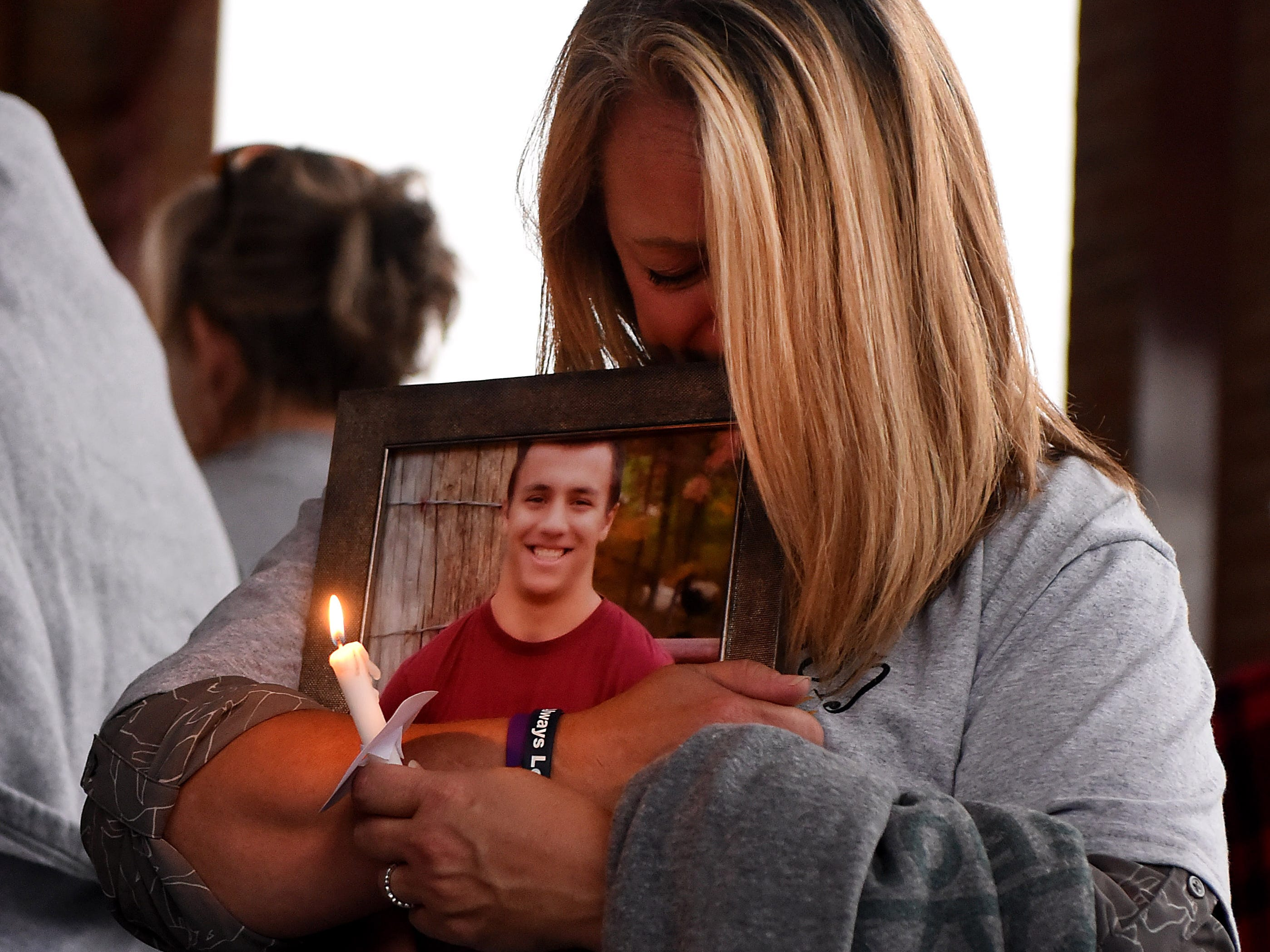 Kelly Wogan holds a photograph of her son, Tommy, during Mental Health America of Licking County's suicide prevention walk and candlelight vigil on Tuesday, Sept. 11, 2018 at the Canal Market District. Tommy, a Licking Valley graduate, died by suicide in January 2018. His parents came to the event to raise awareness and remember their son. The annual event is in recognition of September being Suicide Prevention Awareness month. The event is sponsored by MHA, Licking County Suicide Prevention Coalition, Survivors After Suicide Loss Support Group, and Mental Health & Recovery for Licking and Knox Counties. The Survivors After Suicide Loss Support Group meets at 6:30 p.m. the second Tuesday of every month at Mental Health America of Licking County, 65 Messimer Dr. in Newark.