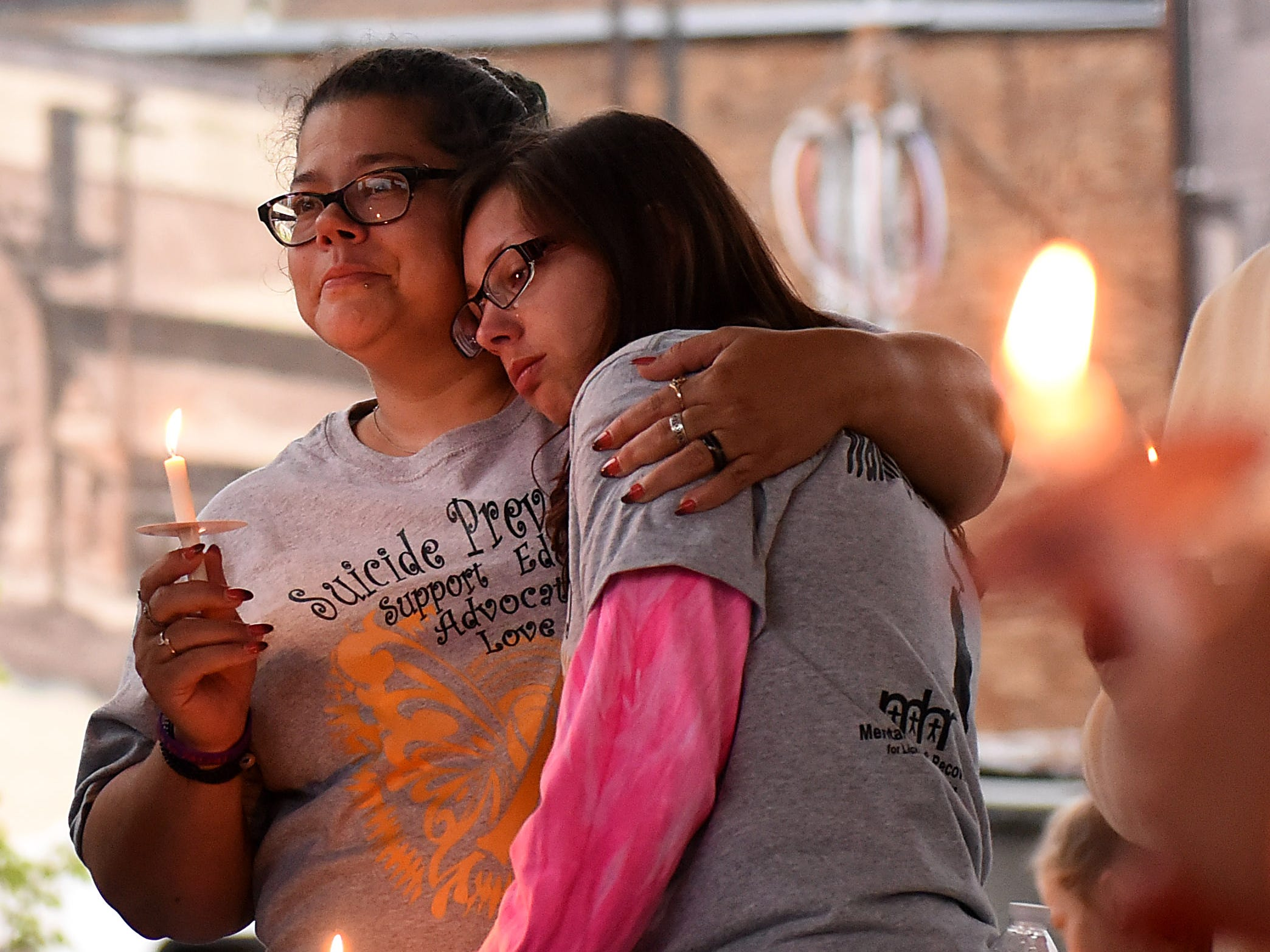 Danielle DeCarlo holds her daughter, Maria DeCarlo, during Mental Health America of Licking County's suicide prevention walk and candlelight vigil on Tuesday, Sept. 11, 2018 at the Canal Market District. Danielle lost her brother in August 2014 and has been attending the event with family every year since his death. The annual event is in recognition of September being Suicide Prevention Awareness month. The event is sponsored by MHA, Licking County Suicide Prevention Coalition, Survivors After Suicide Loss Support Group, and Mental Health & Recovery for Licking and Knox Counties. The Survivors After Suicide Loss Support Group meets at 6:30 p.m. the second Tuesday of every month at Mental Health America of Licking County, 65 Messimer Dr. in Newark.