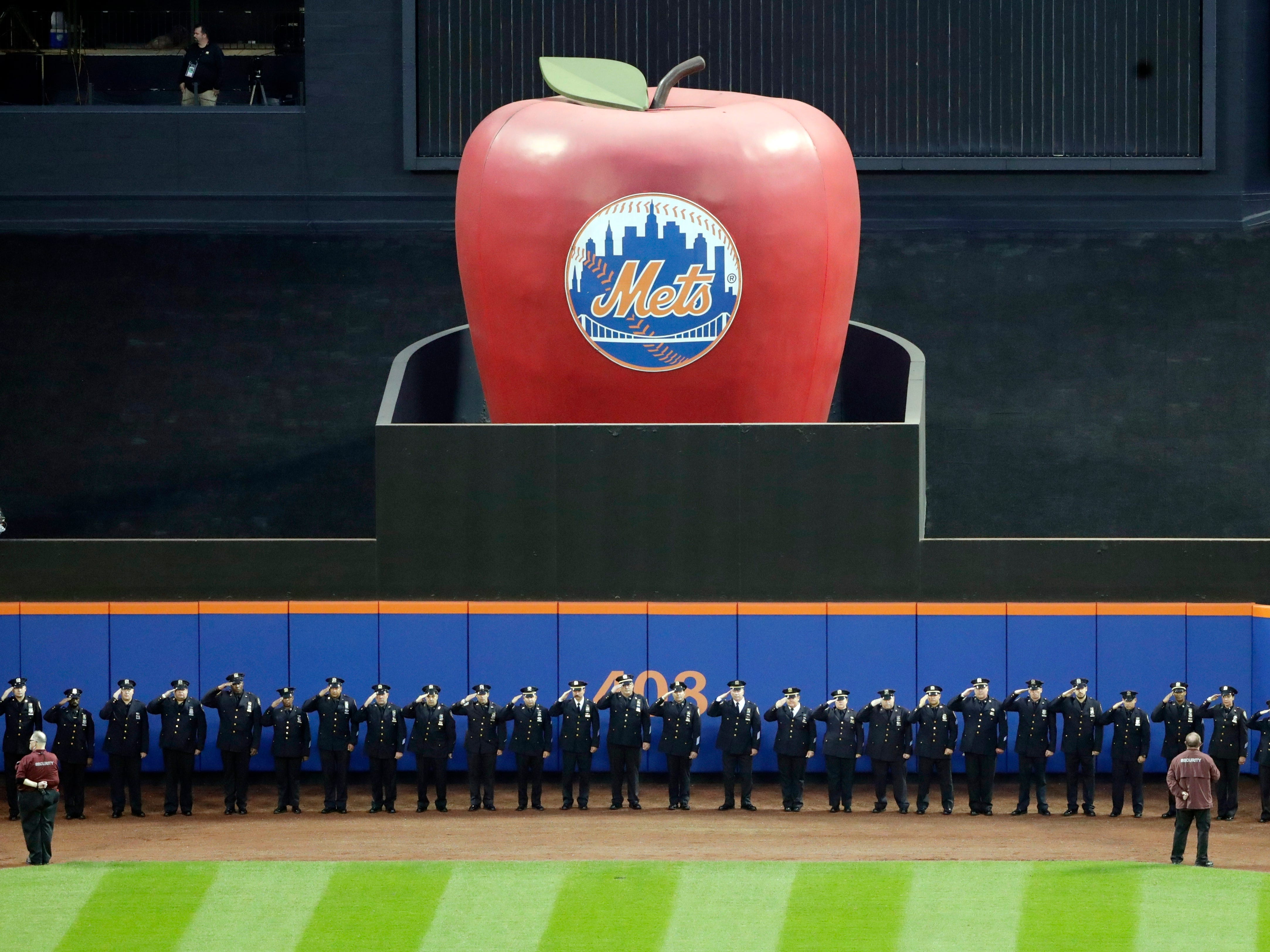 Members of the New York Police Department salute during the pregame ceremony of a baseball game between the New York Mets and the Miami Marlins, Tuesday, Sept. 11, 2018, in New York.