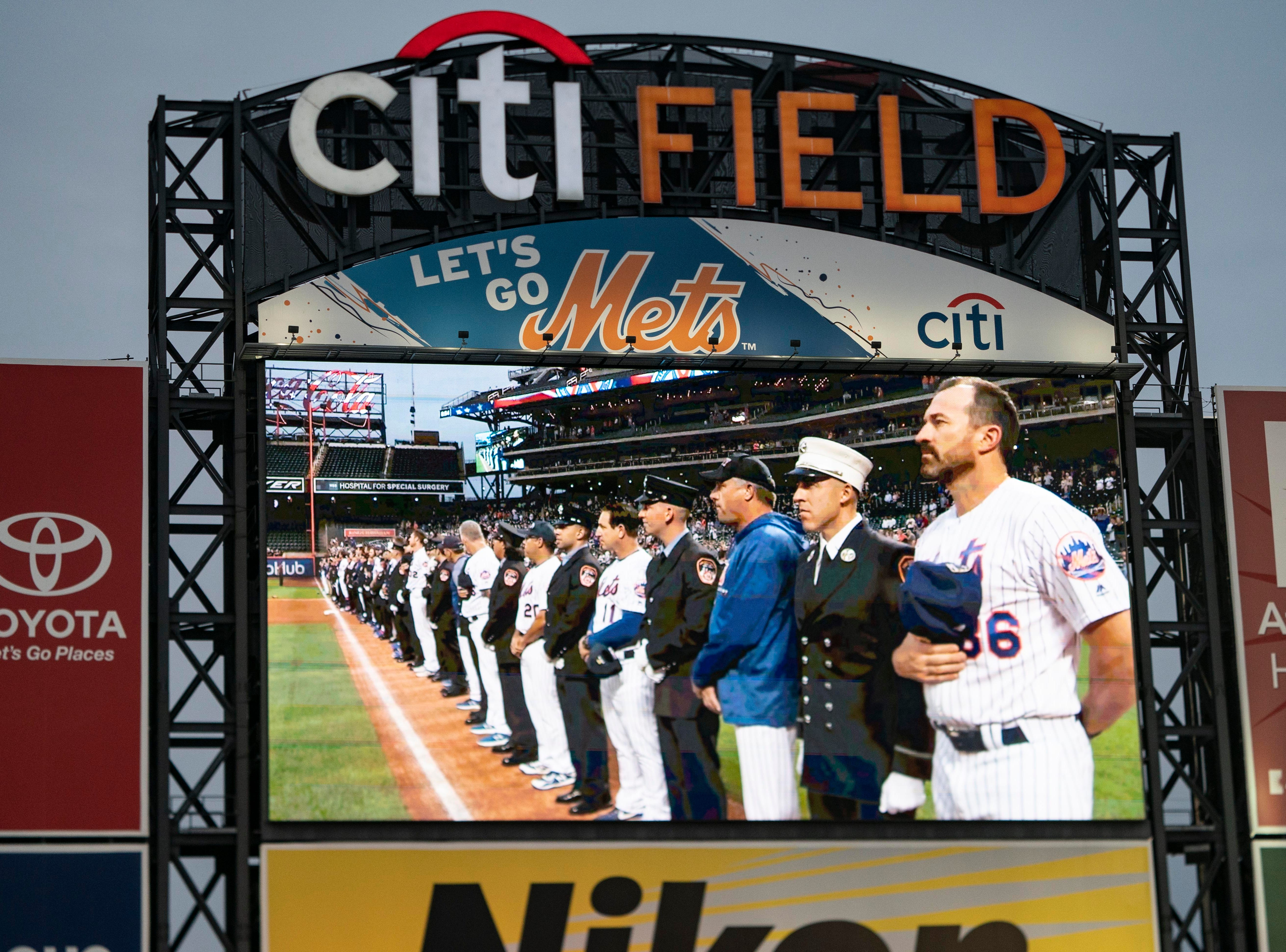 Sep 11, 2018; New York City, NY, USA; Members of New York City first responders stand on the field with the ball players for pregame ceremonies prior to the game at Citi Field.