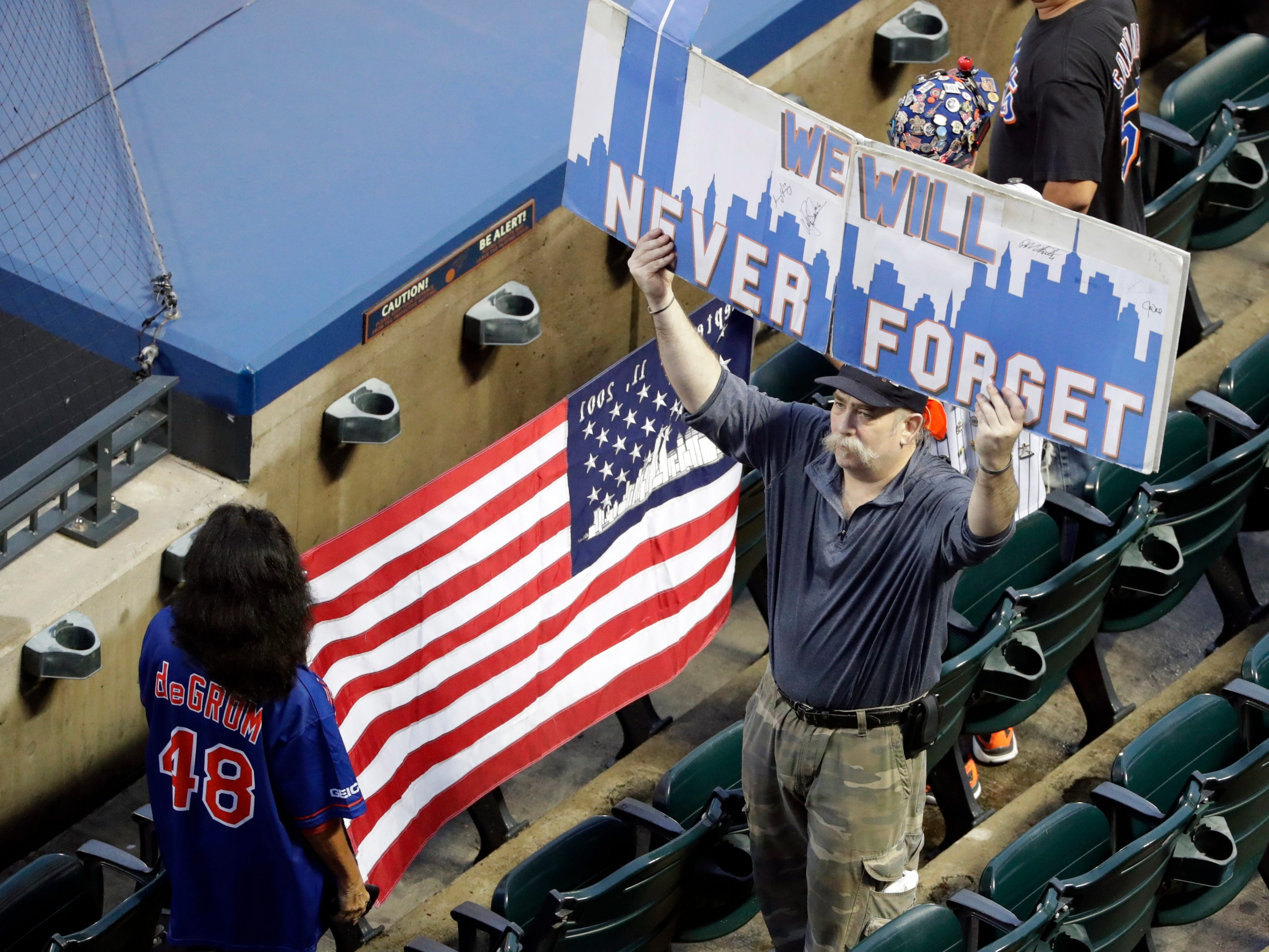 Fans hold up signs before the start of a baseball game between the New York Mets and the Miami Marlins, Tuesday, Sept. 11, 2018, in New York.