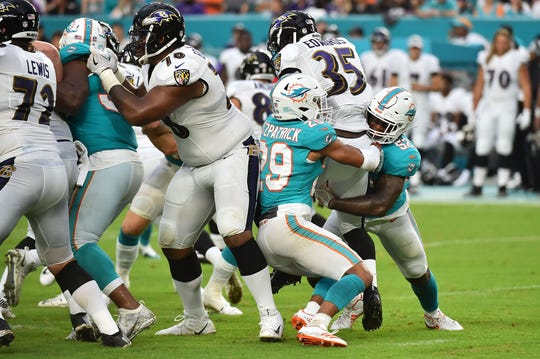 Aug 25, 2018; Miami Gardens, FL, USA; Miami Dolphins linebacker Raekwon McMillan (52) and defensive back Minkah Fitzpatrick (29) bring down Baltimore Ravens running back Gus Edwards (35) during the first half at Hard Rock Stadium. Mandatory