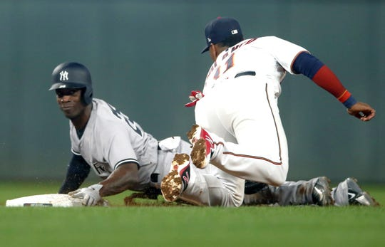 New York Yankees' Andrew McCutchen, left, is tagged out by Minnesota Twins shortstop Jorge Polanco as he attempted to steal second in the third inning of a baseball game Tuesday, Sept. 11, 2018, in Minneapolis.
