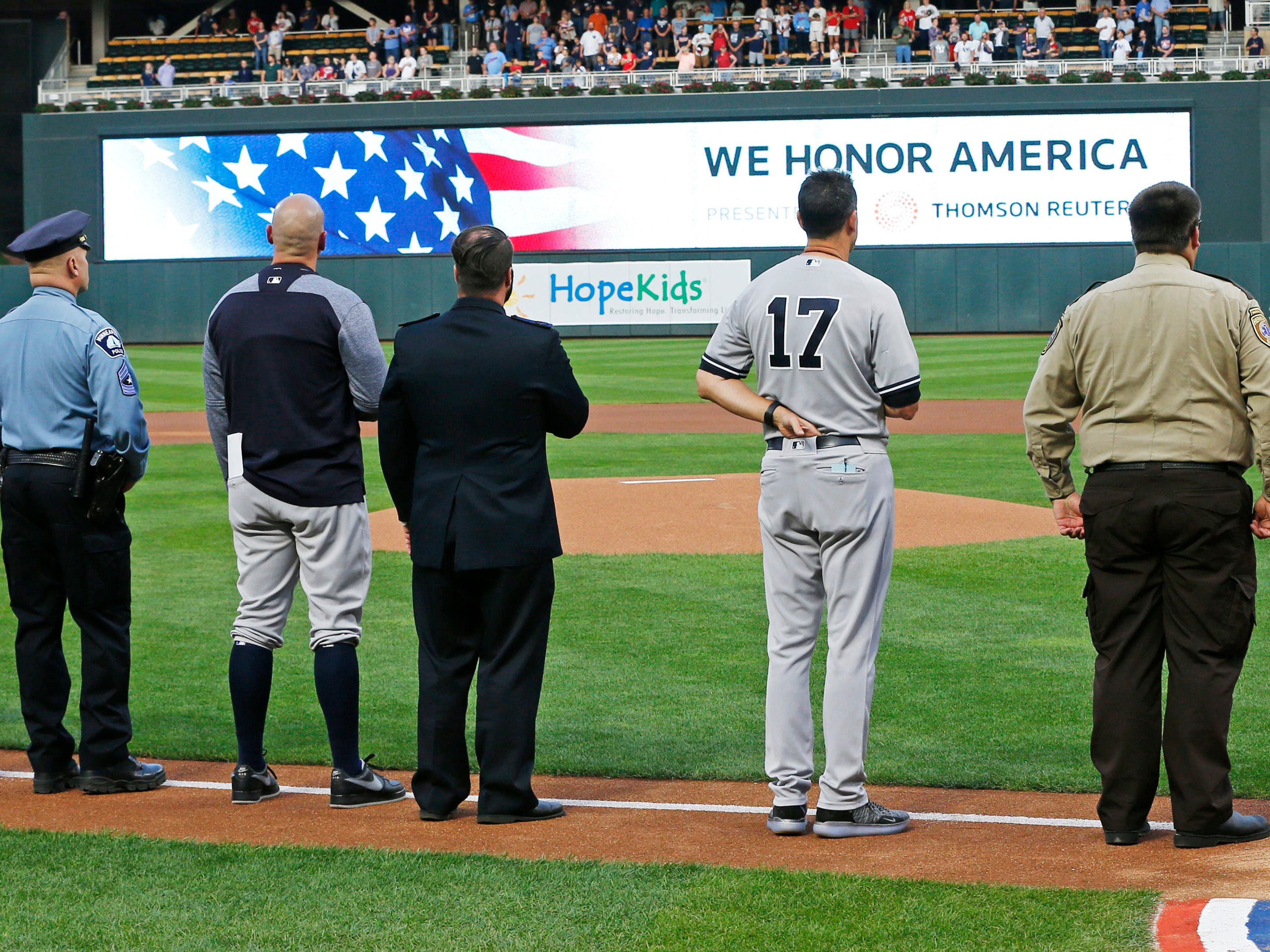 Players from both teams, including New York Yankees manager Aaron Boone (17), joined with police and first responders during the national anthem following a tribute to 9/11 victims and survivors prior to a baseball game between the Minnesota Twins and the Yankees, Tuesday, Sept. 11, 2018, in Minneapolis. Tom Barnett Jr. was aboard Flight 93 which went down in Pennsylvania.