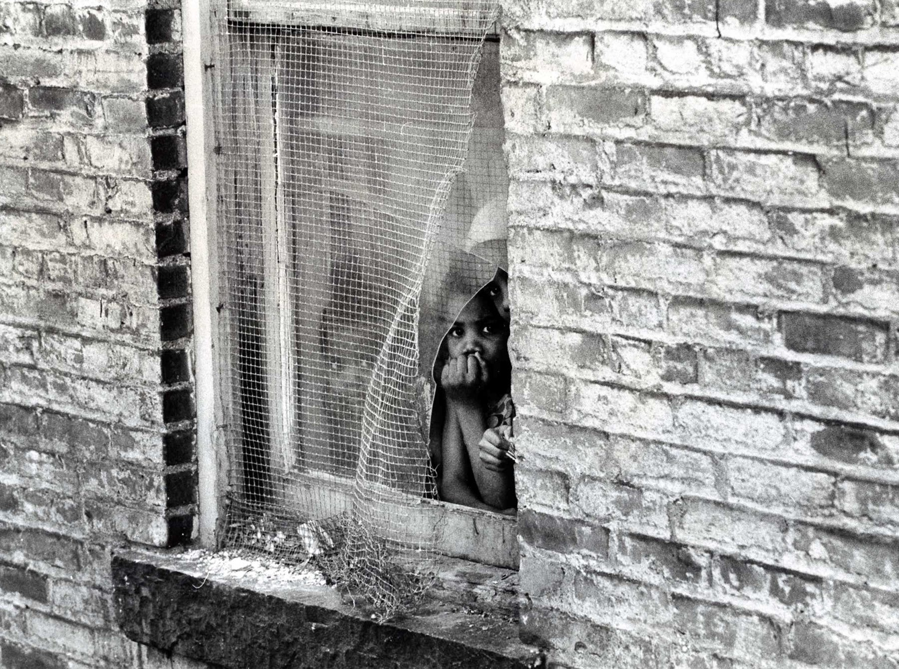Children peak out of a battered tenement window in March 1973.