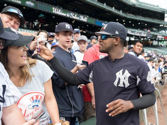 New York Yankees starting pitcher Luis Severino signs autographs before a baseball game against the Seattle Mariners, Sunday, Sept. 9, 2018, in Seattle.