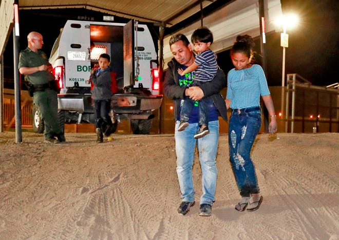 In this July 18, 2018 file photo, a Honduran man carries his 3-year-old son as his daughter and other son follow to a transport vehicle after being detained by U.S. Customs and Border Patrol agents in San Luis, Ariz. Border arrests figures for August 2018, are the latest reminder of how crossings have shifted over the last decade from predominantly Mexican men to Central American families and children. The number of family arrivals reached 15,955, a sharp increase from July that Customs and Border Protection Commissioner Kevin McAleenan said was one of the highest on record.