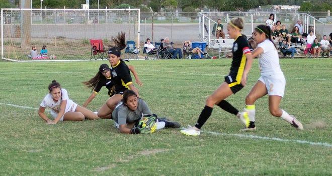 Alamogordo Lady Tigers Shawna Williams (13) and Sydney Dorchester (5) trip and fall over Mayfield Lady Trojan goal keeper Stephanie Tarango, while Sheyenne Drake (2) manages to stay upright.