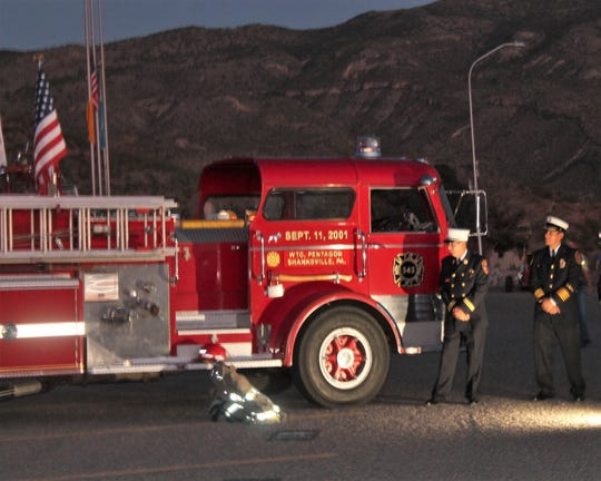 Archie Koenemund, left, stands next to his restored a 1968 Mack C Model fire truck at the Alamogordo 9/11 Memorial Tuesday.