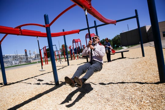 Sanjay Engineer, vice president of FBT Architects, takes a ride on McCormick Elementary School's new playground zip line during a school tour Wednesday in Farmington.