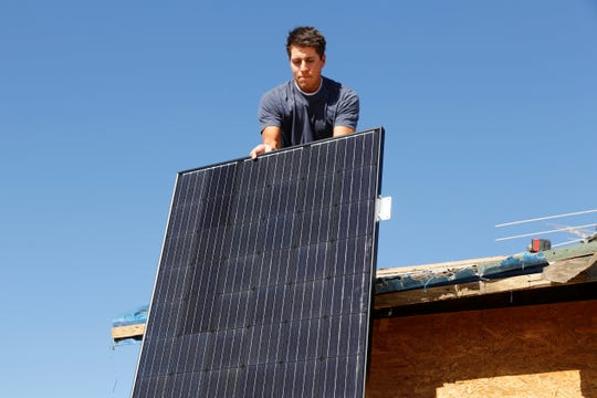 Solar panels are attached to the east and west sides of the roof of the Tahe home on Wednesday in Sanostee.