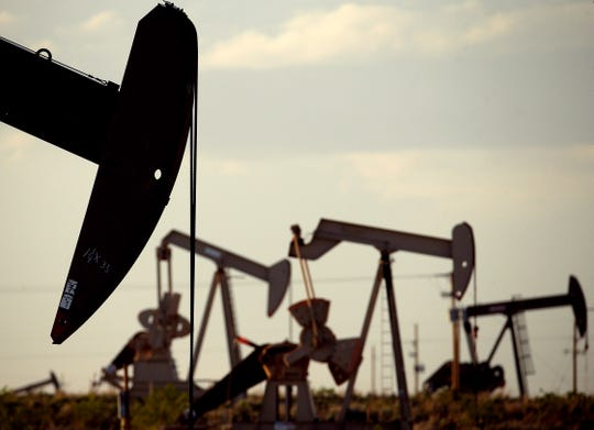 In this April 24, 2015 file photo, pumpjacks work in a field near Lovington, N.M. The United States may have reclaimed the title of the world's biggest oil producer sooner than expected.