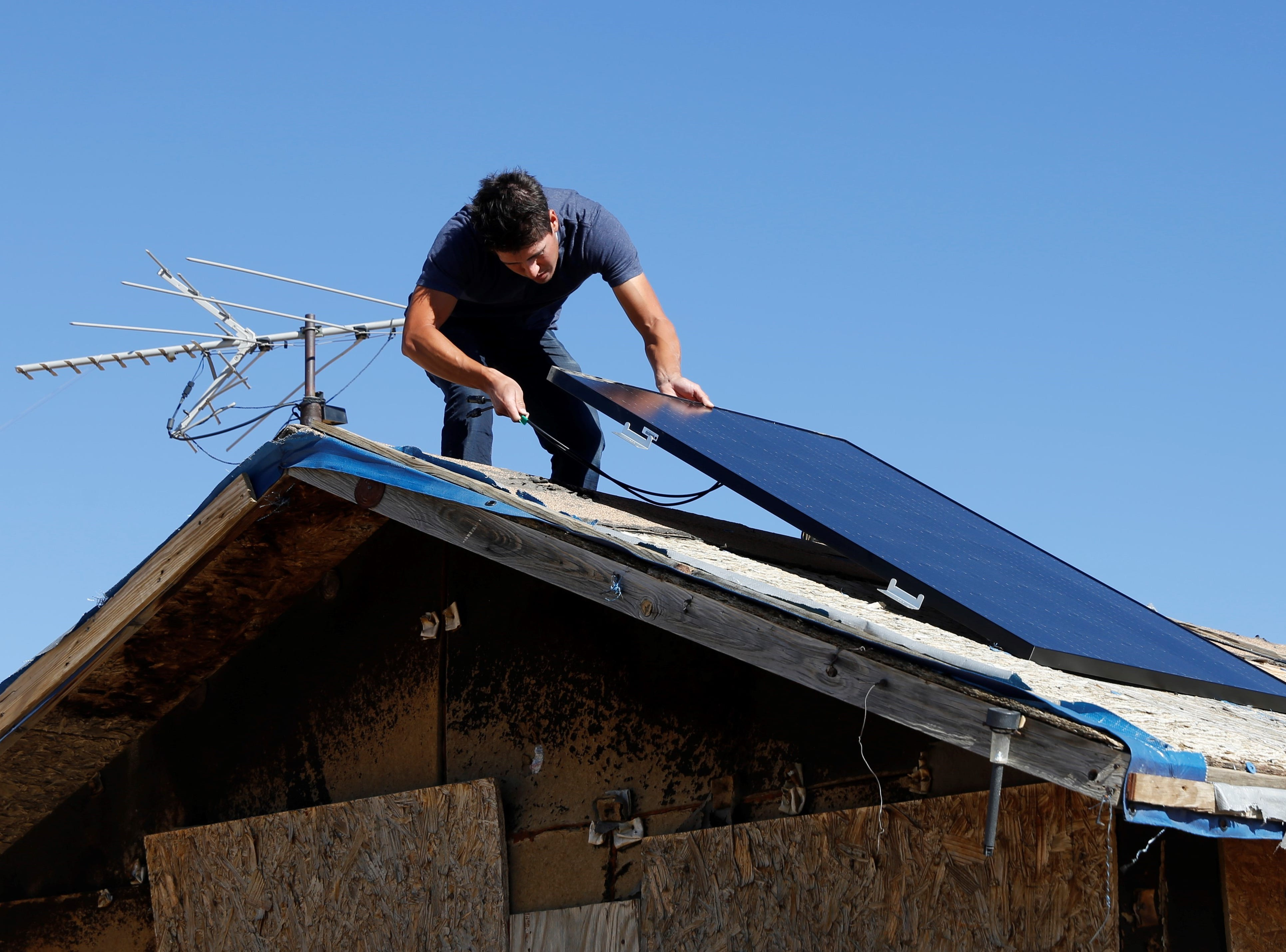 Christian Peters, vice president of operations for Big Navajo Energy, places a solar panel on the east side of the Tahe family home on Wednesday in Sanostee.