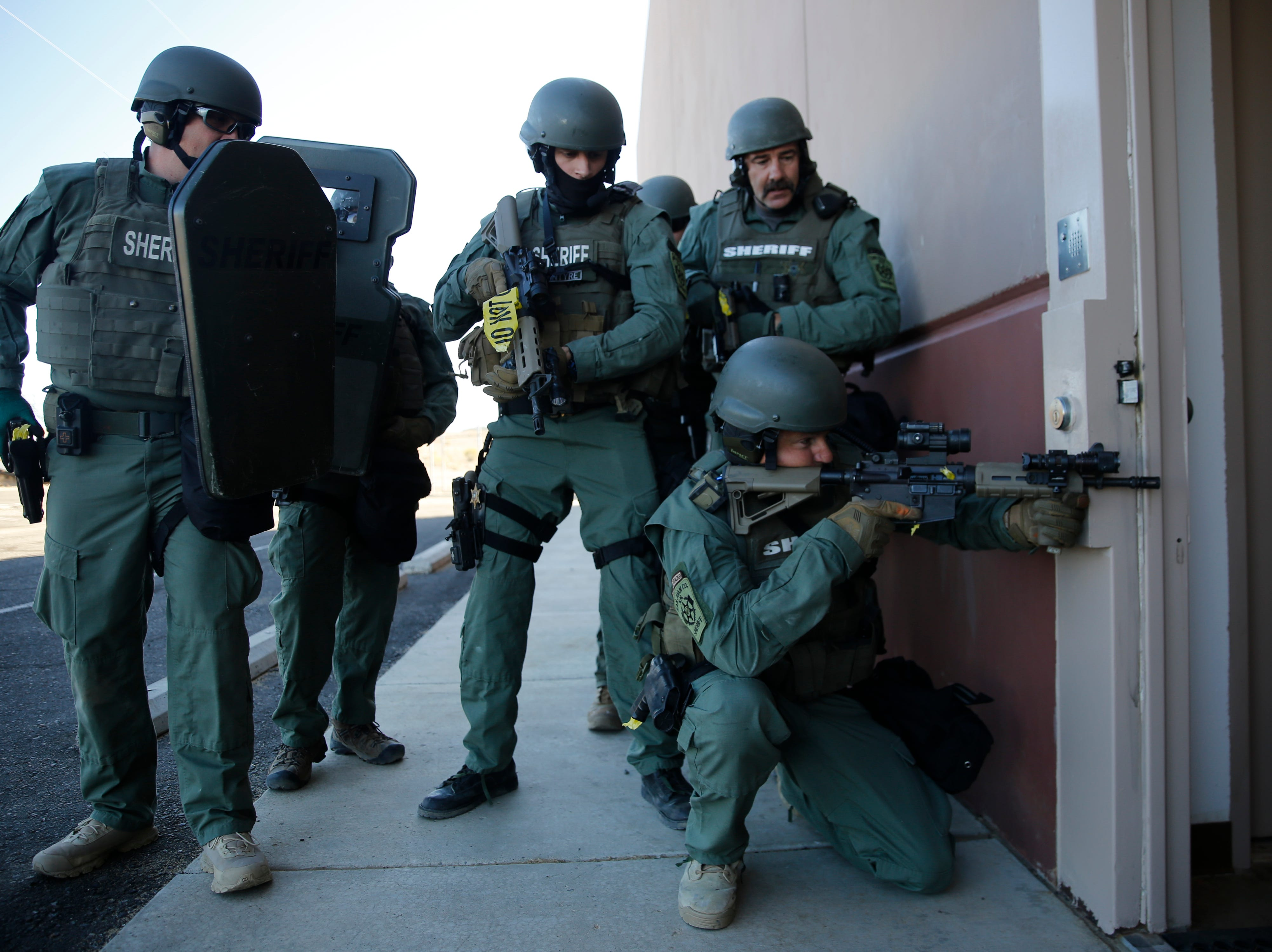 San Juan County Sheriff's Office SWAT team deputies stage at the side entrance of the San Juan County Detention Center, Wednesday, Sept. 12, 2018 during a simulated prison riot in Farmington.