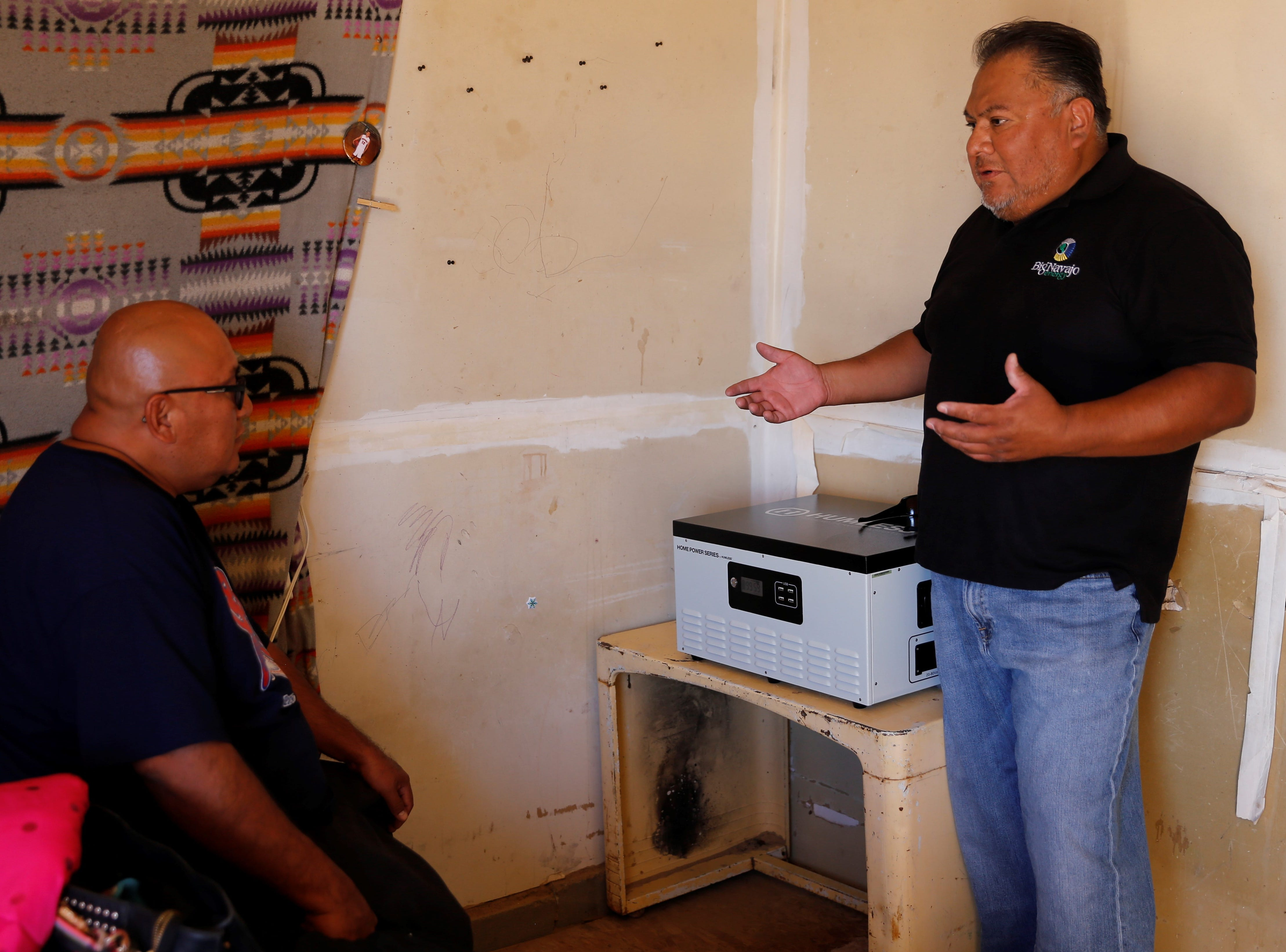 Big Navajo Energy President Dory Peters, right, provides information to Lorenzo Tahe, left, about the solar-powered generator placed inside his home on Wednesday in Sanostee.